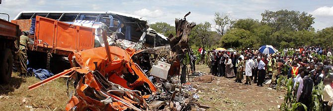 Spectators gather at the scene of a crash after a Zambia postal service bus carrying 74 passengers collided head-on with a heavy goods truck on February 7, 2013 in Chibombo, police say. Sources say the death toll is believed to have risen to 59. Zambia Army and police officers helped in the rescue efforts at the accident scene 45 kilometres north of Lusaka.  AFP PHOTO / STRINGER